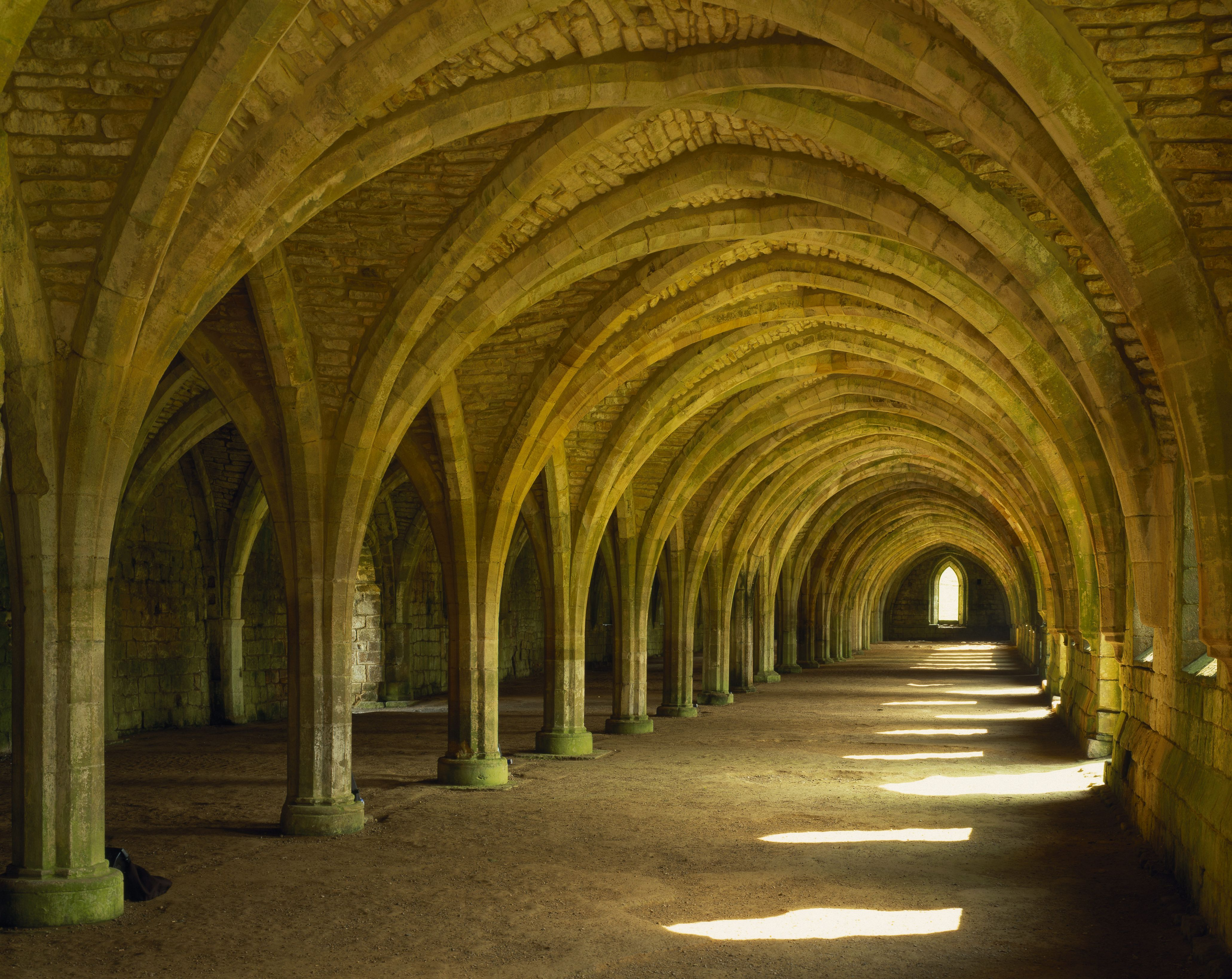 The magnificent West Range of the Cloisters at Fountains Abbey, North Yorkshire, containing the cellarium and lay brothers' refectory.